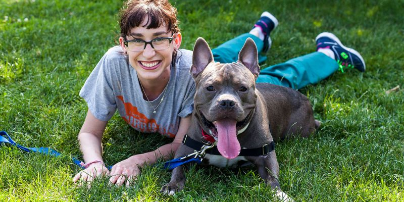 adopter lying on grass with gray pit type dog smiling