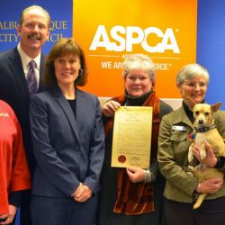group of men and women with ASPCA logo, dog and podium