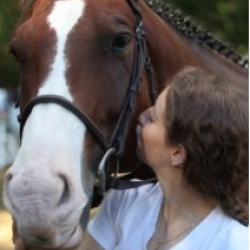 woman kissing brown and white horse face