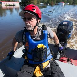 dick green operates a motor boat during a flooding disaster