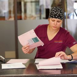 woman in scrubs doing paperwork in a clinical setting