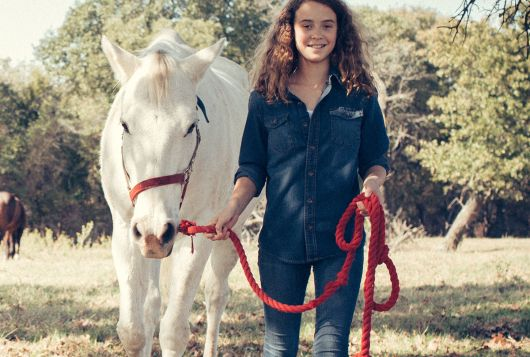 young girl with white horse on lead