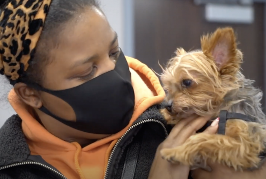 woman holds small dog after services at bronx cvc