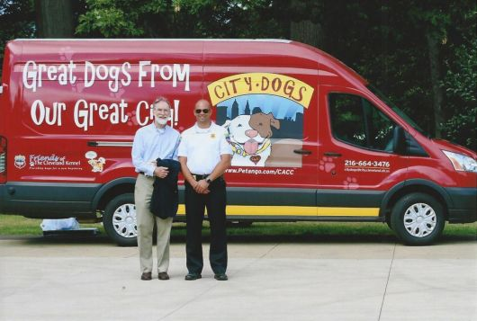 two men standing at van that transports dogs