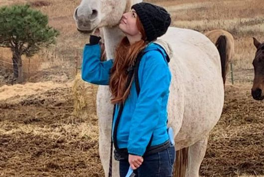 girl stands looking at white horse lovingly