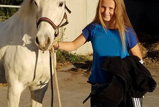 young girl stands smiling next to her horse