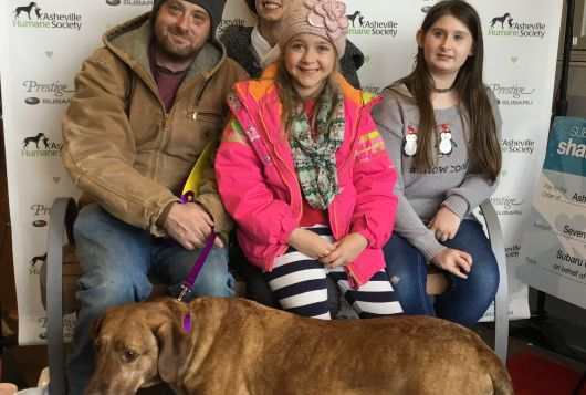 family seated at shelter smiling with new dog