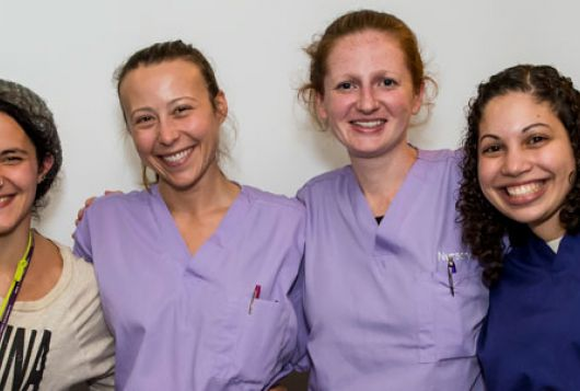 three women in scrubs smiling