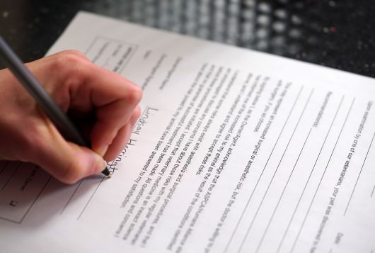 left-handed person signing a form