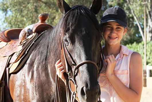 young girl standing lovingly with dark brown horse