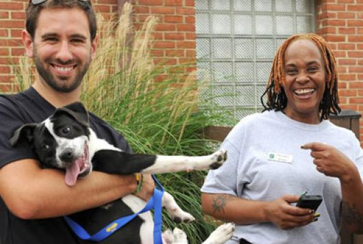 man holding dog and woman outside shelter smiling and laughing