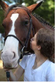 woman kissing brown and white horse in its cheek