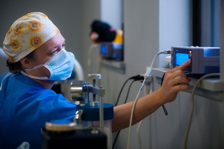 man in blue scrubs and mask working with machine in medical setting