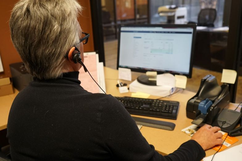 staff member on phone headset at computer