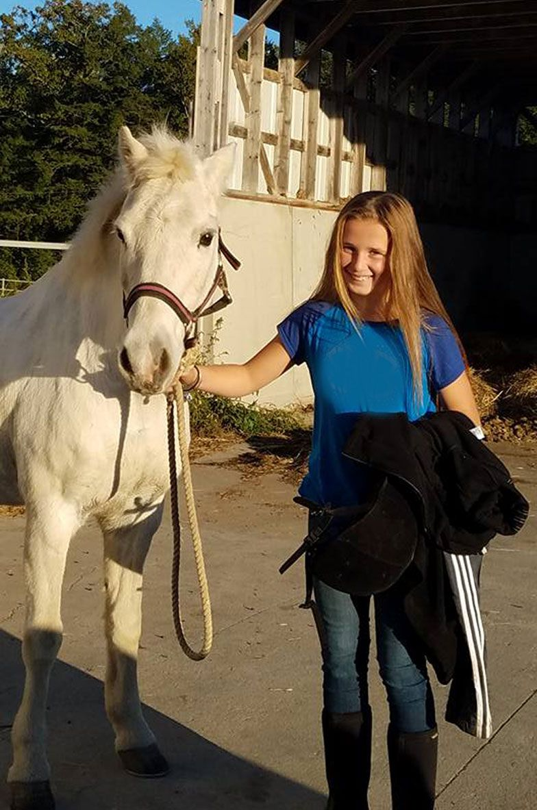 young girl blond hair white horse smiling