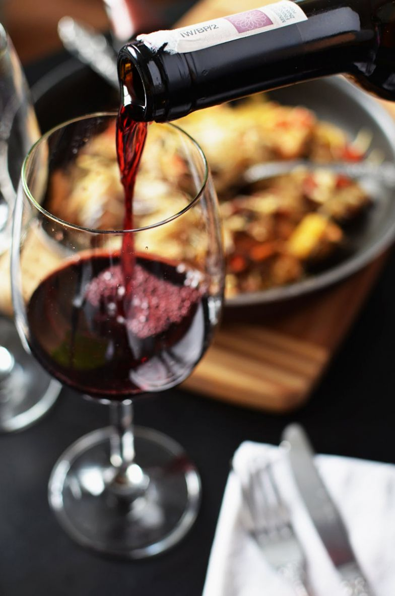wine on table with food, napkin and utensils